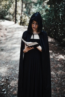 Sorcière à capuchon avec livre dans la forêt en journée