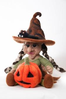 Sorcière avec citrouille un jouet comme cadeau pour halloween. feutre à la main