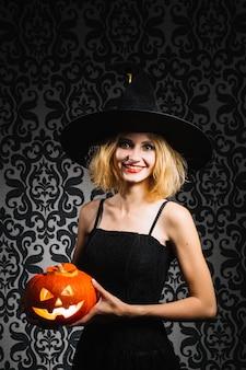 Une sorcière avec une citrouille souriante à la caméra