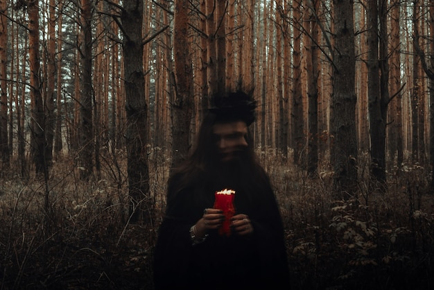 Sorcière en costume noir exécute des sorts sombres avec des bougies dans la forêt. photo floue avec flou en raison de la longue durée d'exposition