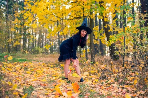Sorcière dans la forêt d'automne. cosplay d'halloween. célébration des vacances d'automne d'halloween. belle femme de race blanche en costume withch