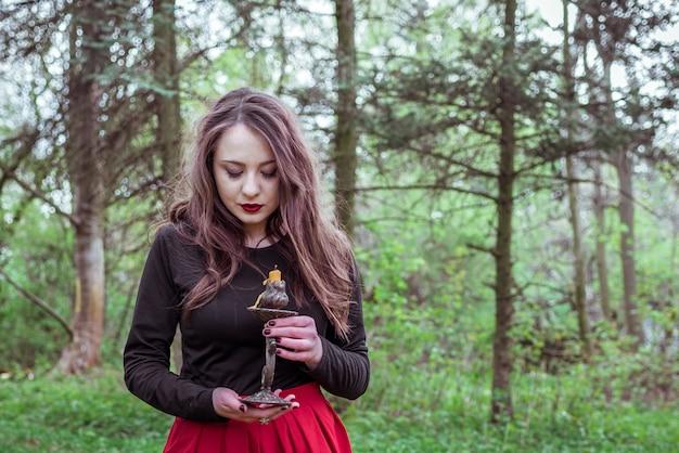 Sorcière dans la forêt avec une bougie