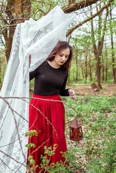 Sorcière dans la forêt avec une lanterne