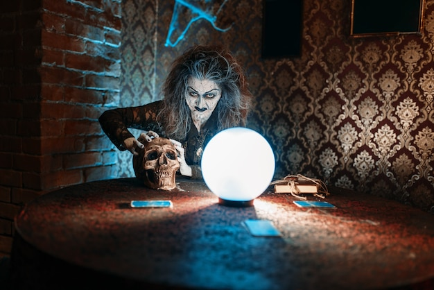 Sorcière effrayante avec crâne humain lit un sort magique sur une boule de cristal