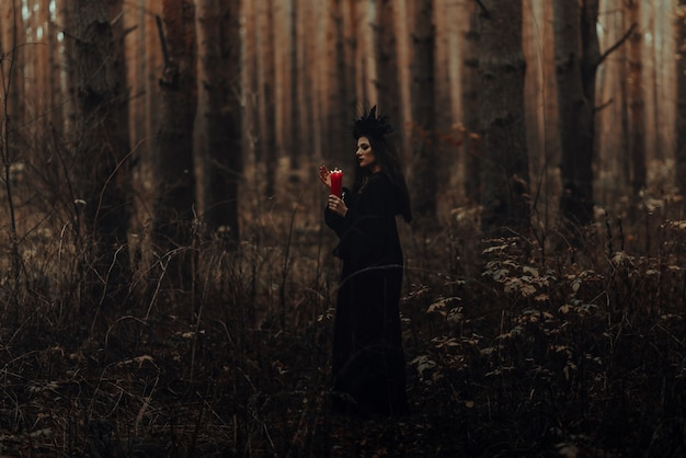Sorcière effrayante effectue un rituel occulte avec des bougies dans une sombre forêt sombre