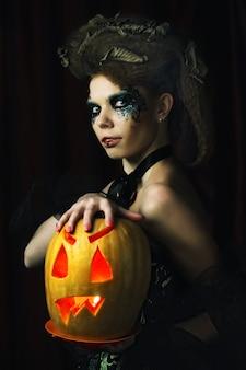 Sorcière d'halloween avec citrouille sculptée sur fond rouge.