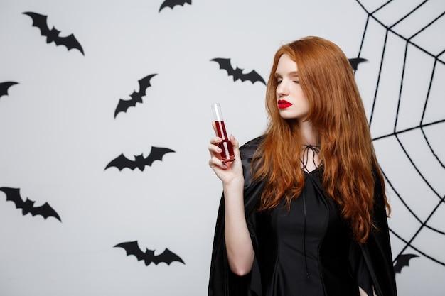 Sorcière de halloween heureux, boire du sang sur fond de studio gris foncé avec chauve-souris et toile d'araignée.