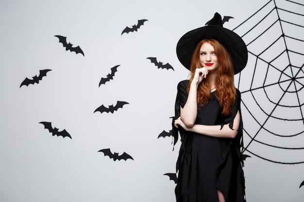 Sorcière d'halloween heureux tenant posant sur fond de studio gris foncé avec chauve-souris et toile d'araignée.