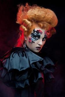 Sorcière rousse gothique. femme noire. maquillage artistique. photo d'halloween.