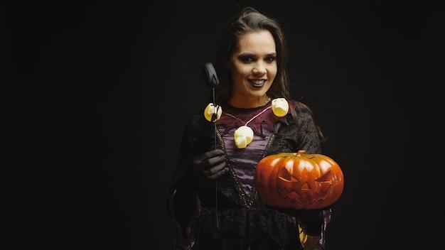 Sorcière souriante habillée pour halloween tenant la citrouille sur fond noir.