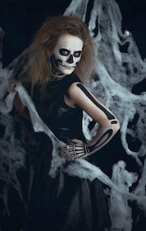 Sorcière squelette fille posant dans les toiles, halloween. la sorcière se prépare pour la nuit des morts