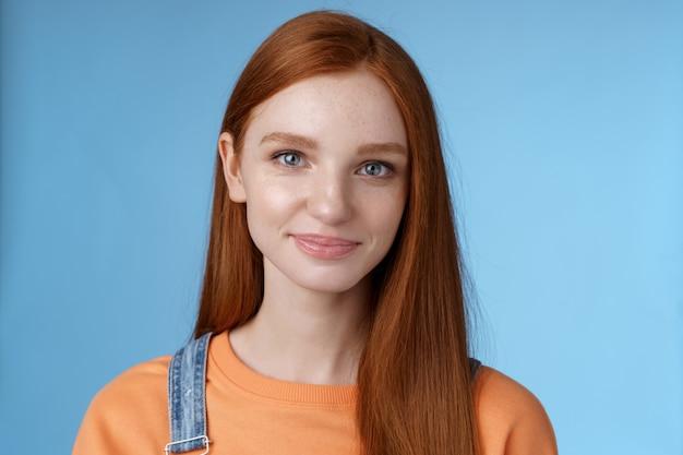 Sortant jeune fille rousse yeux bleus portant une salopette tshirt orange souriant agréablement avec désinvolture parler debout bonne humeur émotions joyeuses fond bleu écoute conversation intéressante