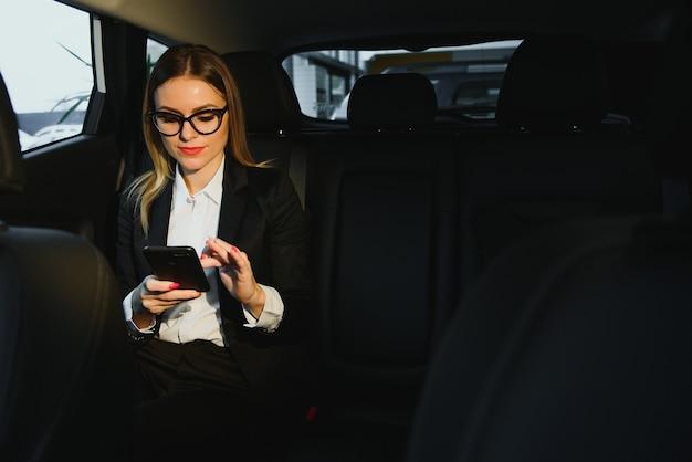 Une sorte d'informations intéressantes. smart businesswoman est assis à l'arrière de la voiture de luxe avec intérieur noir.