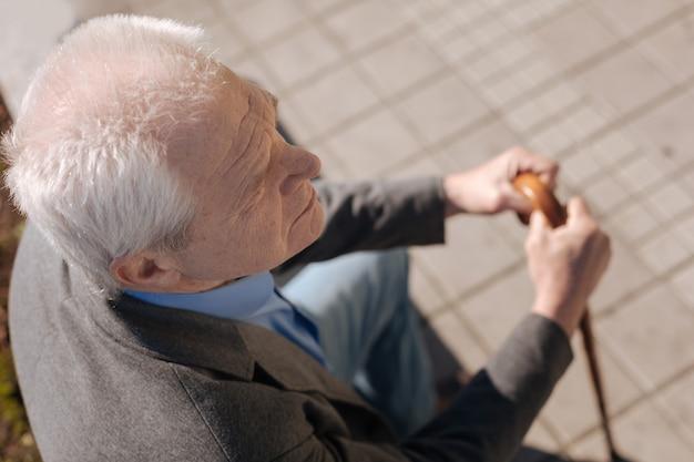 Sorti de la retraite émotionnellement mignonne regardant vers l'horizon et attendant chères personnes tout en se reposant sur le banc