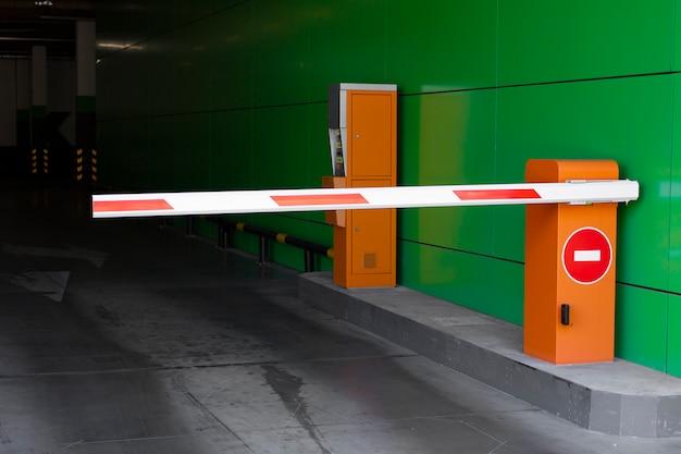 La sortie du parking est fermée par une barrière. panneau stop.