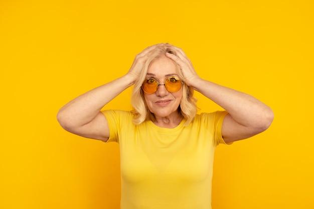 Sortie jolie femelle adulte en t jaune et lunettes de soleil orange avec ses mains sur la tête.