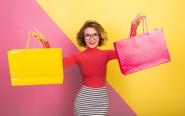 Sortie jolie femme en tenue colorée élégante tenant des sacs à provisions