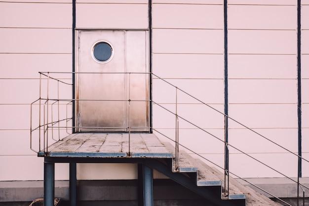Sortie de secours vue de la rue, avec un escalier en béton et des tons neutres.