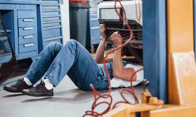 Sortir. l'employé en uniforme de couleur bleue travaille dans le salon automobile.