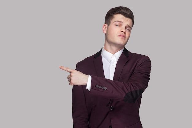Sortir. portrait d'un beau jeune homme sérieux en costume violet et chemise blanche, debout, regardant la caméra avec un visage en colère et montrant le côté sortie. tourné en studio intérieur, isolé sur fond gris.