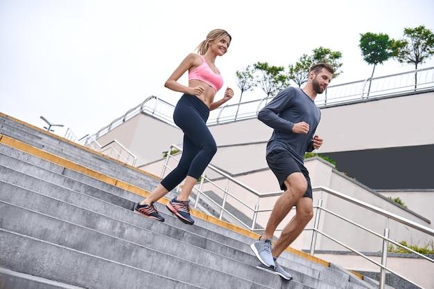 Sortir pour une course sur toute la longueur du jeune couple en vêtements de sport qui traverse le