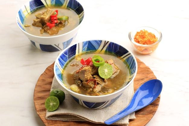 Soto sapi ou soto daging, est une soupe spéciale indonésienne. ce plat à base de bouillon de boeuf avec escalope de viande. servi sur un bol en céramique blanc et bleu. menu populaire pour idul adha