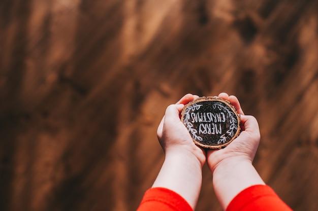 Souche de bois dans les mains des enfants avec les mots, joyeux noël