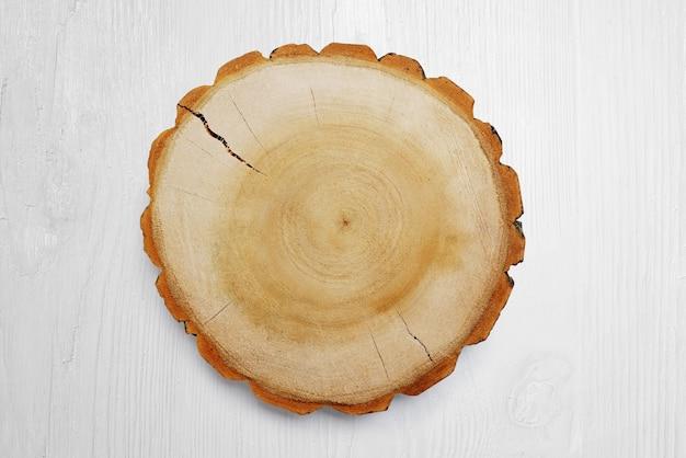 Souche en bois sur le fond blanc. arbre coupé rond avec des cernes annuels comme texture de bois