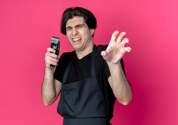 Souci jeune beau coiffeur masculin en uniforme tenant une tondeuse à cheveux et montrant le geste de style tigre isolé sur rose