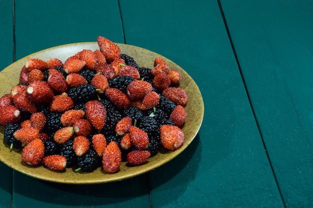 Une soucoupe avec des fraises et des mûres se dresse sur une table verte en bois à gauche