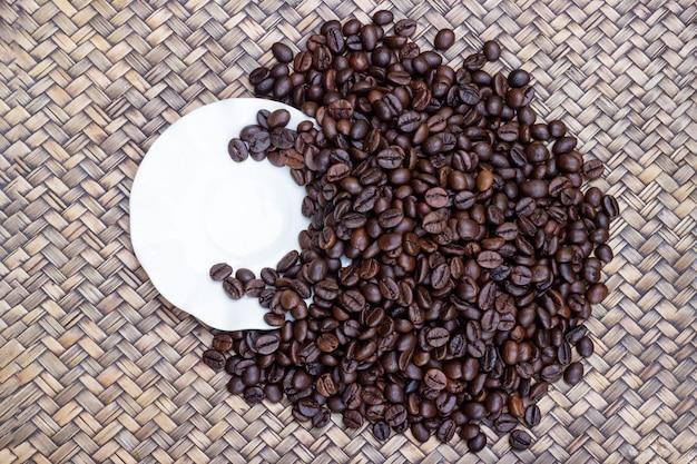 Soucoupe tasse à café avec des grains de café placés sur un plateau en bois.
