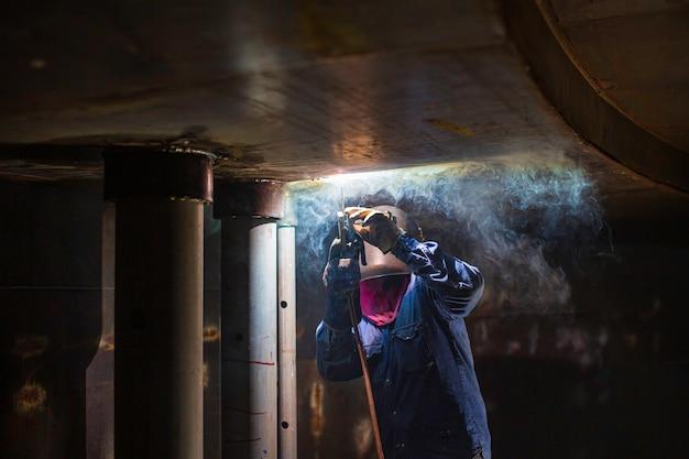 Le soudage à l'arc métallique du travailleur masculin fait partie de la construction du pipeline de la buse du réservoir des machines, du réservoir de stockage de pétrole et de gaz à l'intérieur d'espaces confinés.