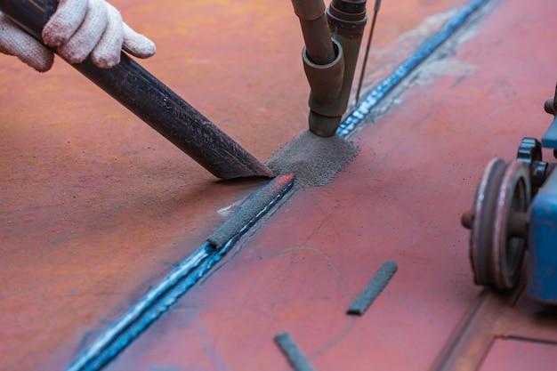 Soudage du revêtement dur du rouleau d'acier de la plaque de fond du réservoir par procédé de soudage à l'arc sous laitier.