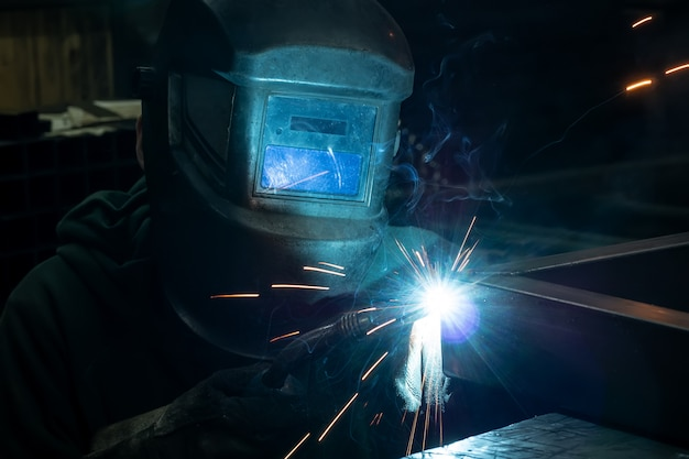 Le soudeur cuit le cadre. le soudeur cuit le métal. le soudeur cuisine des structures métalliques. travaux de soudure. étincelles, métal fondu