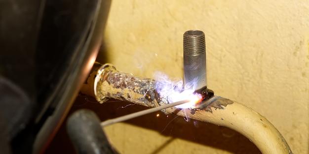 Soudeur professionnel soudant avec de vieux tuyaux métalliques électriques pour le chauffage. ancien concept de rénovation de système de chauffage