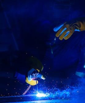 Le soudeur soude l'acier ensemble pour le rendre plus solide. le travail produit des étincelles brillantes avec de la fumée, l'effet de la lumière et de la fumée lui donne une belle lumière bleue. l'arc est un domaine spécialisé qui nécessite des compétences.