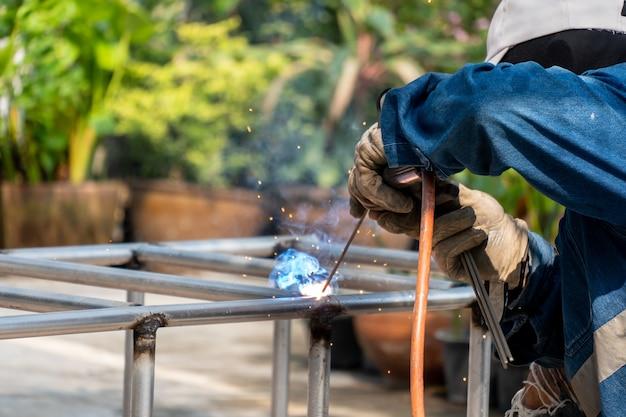 Le soudeur soude le cadre en acier. la main-d'œuvre et l'industrie travaillent dur.