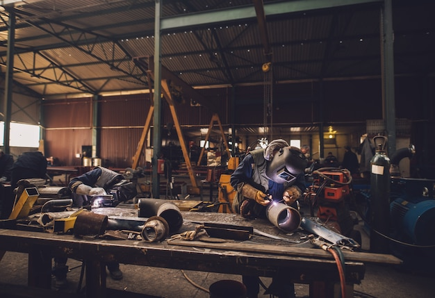 Soudeur en uniforme de protection et masque de soudure de tuyau métallique sur la table industrielle pendant que des étincelles volent.