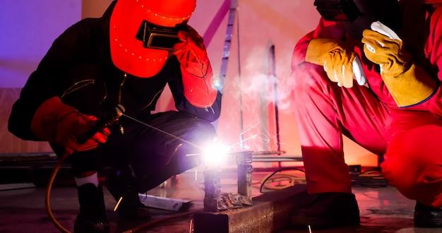 Soudeurs masculins travaillant ensemble sur le site.