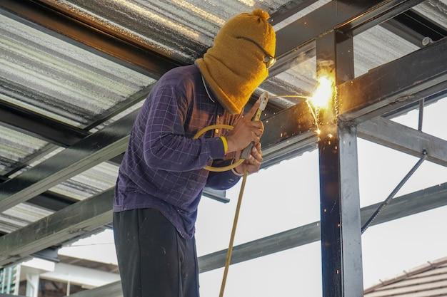 Les soudeurs soudent le cadre de toit en acier de la maison