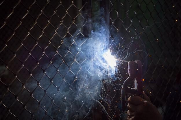 Les soudeurs soudent les portes pour protéger la propriété sur un fond sombre
