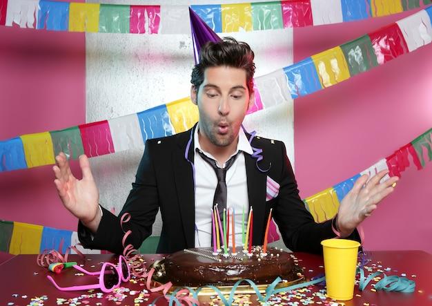 Soufflant jeune homme un gâteau de fête au chocolat
