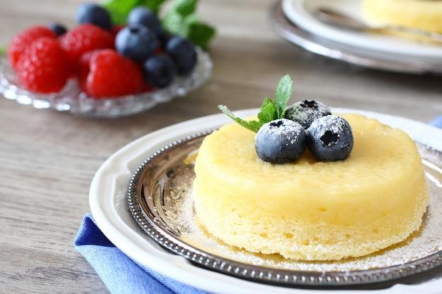 Soufflé au citron et éponge servi avec des baies sur une assiette