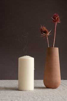 Soufflé bougie aromatique et vase en argile brune à la main ou une cruche avec deux fleurs sauvages sèches debout sur la table sur le mur noir