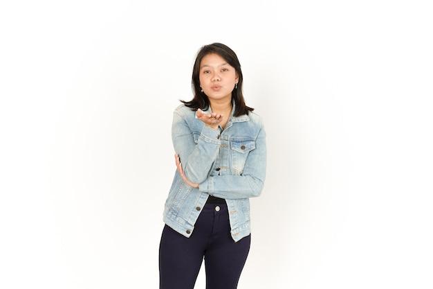 Souffler le baiser de la belle femme asiatique portant une veste en jean et une chemise noire isolée sur blanc