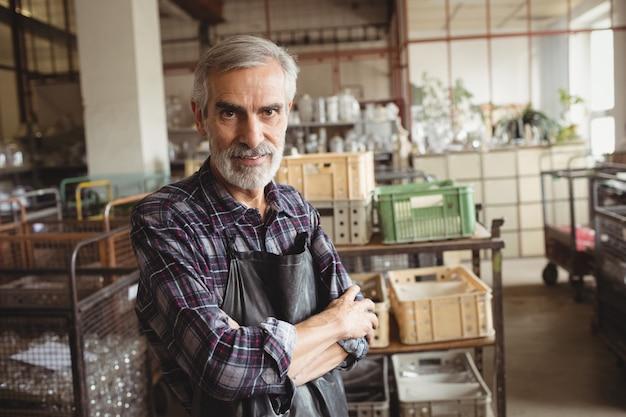 Souffleur de verre debout avec les bras croisés à l'usine de soufflage de verre