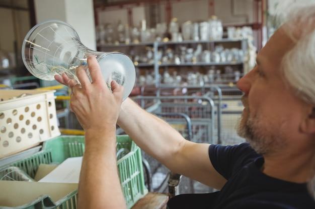 Souffleur de verre examinant la verrerie