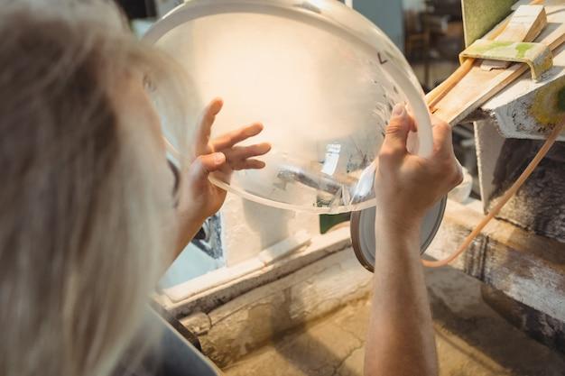 Souffleur de verre polissant et rectifiant une verrerie