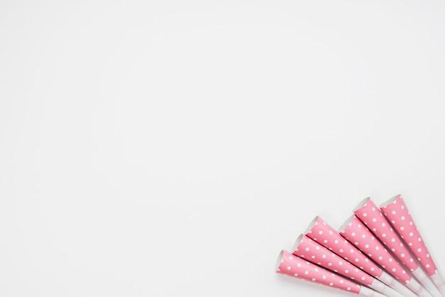 Souffleurs de corne de fête à pois sur le coin de la toile de fond blanche