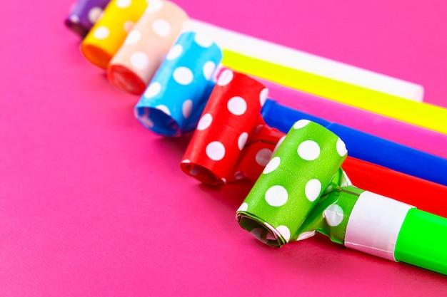 Souffleurs multicolores sur rose. sifflets de fête multicolores. décor pour un anniversaire.